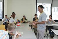 New York, NY, USA - June 23, 2012: Sipho Mabona teaches a class how to fold his original design, a complex origami bear.