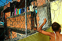 Two girls talking to each other on the rooftops of the Rocinha favela. The biggest slum in Brazil, built on a steep hillside overlooking the city, just one kilometre from the beach. Rio de Janeiro, Brazil, 2008