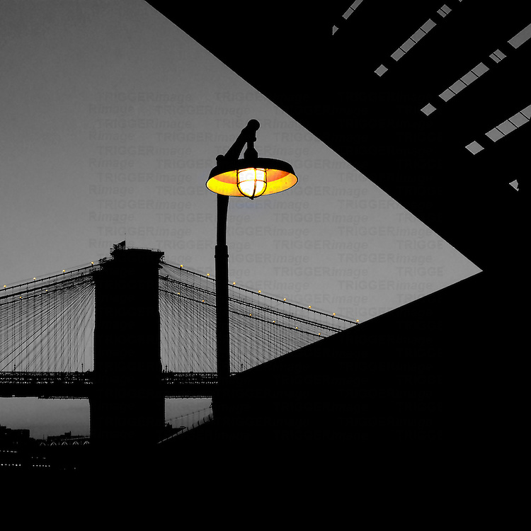 Silhouette of Brooklyn Bridge with a street lamp, shot from Pier 17, New York City.