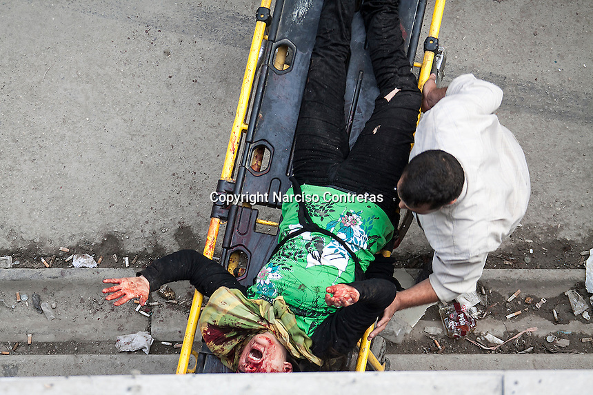 A Syrian man wheels a severely injured woman to the Dar Al-Shifa hospital for treatment after an artillery shell landed near a bakery in Aleppo, Syria. October 23, 2012.