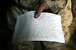 "LCpl. John Baldonado - 3rd Platoon Echo Company 2nd Battalion 5th Marines - holds the citation read detailing his actions meriting recognition after being awarded the Navy Achievement Medal with a Combat ""V"" for Valor during a ceremony at the company's base - the ""Snake Pit"" - on January 9, 2005 in Ramadi, Iraq. The ceremony also saw three other members of his company awarded Purple Hearts for wounds received in combat."