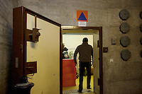 Switzerland. Geneva. A guard from the private security firm (SPS Sécurité) is standing at the entrance door of the fallout shelter Richemond. The security guard is conducting surveillance by watching and checking  identities of homeless people entering the shed. The bunker was constructed as civil defense measures during the Cold War and is a unit of the Civil Protection. Switzerland is unique in having enough nuclear fallout shelters to accommodate its entire population. 9.02.2014 © 2014 Didier Ruef