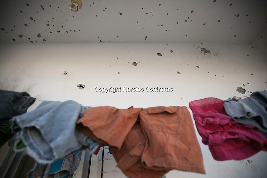 """In this Saturday, Aug. 16, 2014 photo, children's clothes are seen hanging at a family apartment partially distroyed by artillery shelling during the """"Protective Edge"""" Israeli military operation in Beit Hoanoun neighborhood in Gaza City. After a five days truce was declared on 13th August between Hamas and Israel, civilian population went back to what remains from their houses and goods in Gaza Strip. (Photo/Narciso Contreras)"""