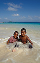 Marshall Islands, Micronesia: Two boys sitting in the lagoon water at Calalin Island, a &quot;Picnic Island&quot; on Majuro Atoll..