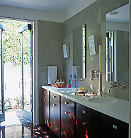 Double wash basins in a red-stained unit with the bathroom walls lined with grey stone tiles and French windows opening onto a garden of grey Mexican pebbles