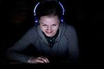 Teenager looking at computer screen in a darken living room