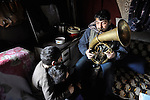 As two of his children look on, Milan Pesic practices his french horn inside his home in a Roma settlement in Belgrade, Serbia, in February 2012. Pesic plays in a Roma band. The families that live here, many of whom survive from recycling cardboard and other materials, are under constant threat of eviction in order to make way for new high-rise office buildings. Note: Pesic and other residents of this settlement were forcibly evicted in April 2012, two months after this photo. Many, including Pesic and his family, were relocated in metal shipping containers at the edge of the city.
