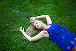 A young woman wearing a blue dress lies on a carpet of fresh green grass in a park.
