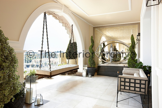 A covered terrace with a swing-seat allows a view through an archway. A mirrored wall creates a sense of space.