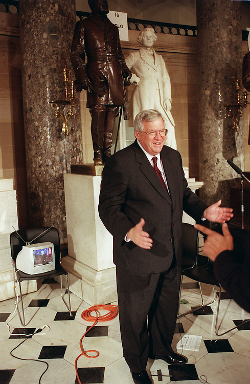 1/27/00.STATE OF THE UNION--House Speaker J. Dennis Hastert, R-Ill., jokes with crew as he prepares to be interviewed for The News Hour with Jim Lehrer in Statuary Hall after President Bill Clinton's State of the Union Address. The Tonight Show with Jay Leno plays on the monitor behind him..CONGRESSIONAL QUARTERLY PHOTO BY SCOTT J. FERRELL