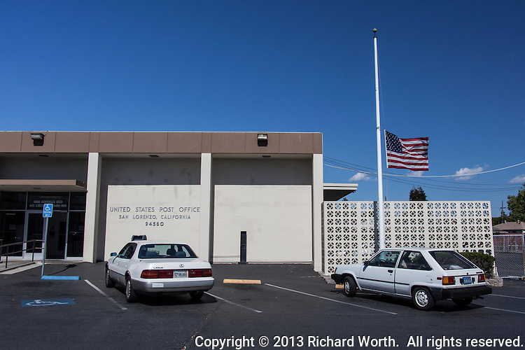 The American flag flies at half mast outside of the US Post Office in San Lorenzo, California, over 3,000 miles away from Boston, Massachusetts and the Boston Marathon bombing.