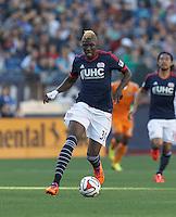 New England Revolution midfielder Saer Sene (39) on the attack.  In a Major League Soccer (MLS) match, the New England Revolution (blue/white) defeated Houston Dynamo (orange), 2-0, at Gillette Stadium on April 12, 2014.
