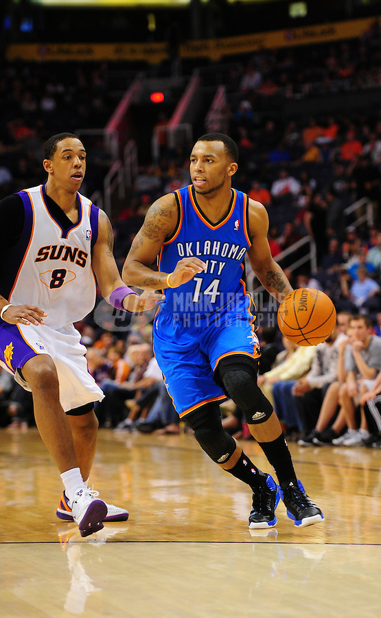 Mar. 30, 2011; Phoenix, AZ, USA; Oklahoma City Thunder guard (14) Daequan Cook controls the ball against Phoenix Suns center (8) Channing Frye at the US Airways Center. Mandatory Credit: Mark J. Rebilas-
