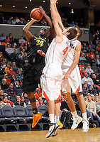 Dec. 17, 2010; Charlottesville, VA, USA; Oregon Ducks forward Joevan Catron (34) shoots the ball in front of Virginia Cavaliers forward Will Regan (4) and Virginia Cavaliers guard Joe Harris (12) during the first half of the game at the John Paul Jones Arena. Mandatory Credit: Andrew Shurtleff