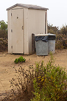 The pit toilet and trash cans at Crystal Cove State Park's Lower Moro campground.