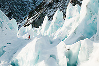 Hiker among ice pinnacles on Franz Josef Glacier in winter, Westland National Park, West Coast, World Heritage Area, South Island, New Zealand
