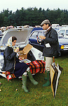 Picnic at polo match Windsor Great Park, the car park. Berkshire England. Circa 1985. Wealthy upper class style, the woman is wearing a Hermes headscarf and blue Burberry waxed jacket as is he plus a flat tweed cap. Shes on Bucks Fizz he's drinking Champagne.1980s.