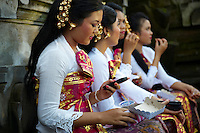 Young balinese woman sending SMS during the wait for the Ubud Festival show to start. Her friends are having a snack.<br />