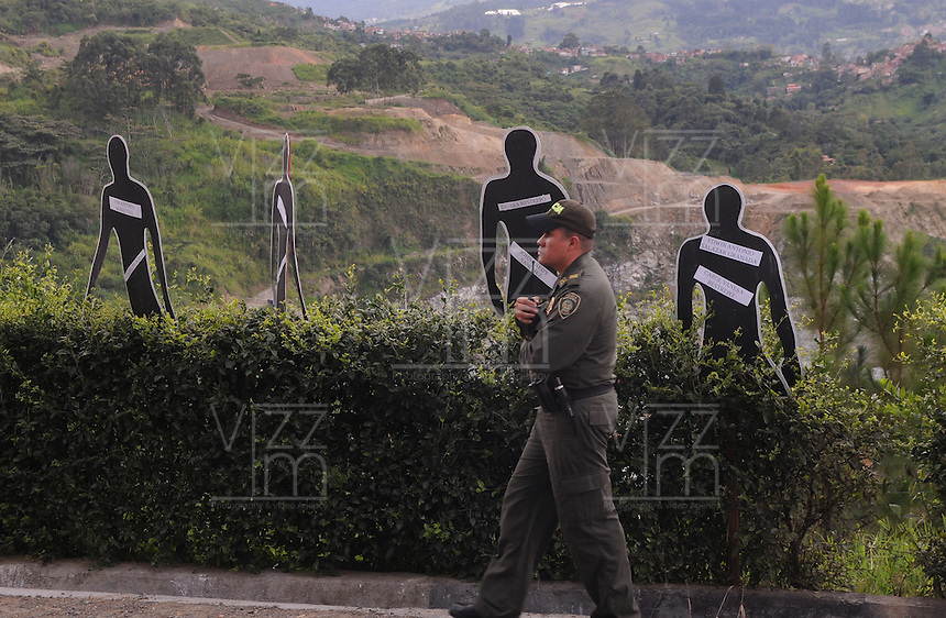 """MEDELLÍN - COLOMBIA, 07-06-2014. Un oficial de policía pasa junto a las siluetas con los nombres de las personas desaparecidas en """"La Escombrera"""", en la Comuna 13 de Medellín, durante una vigilia contra las desapariciones forzadas. En 2002, Medellín fue sacudido por la violencia después de la decisión del Gobierno de recuperar un sector de la ciudad disputada por los paramilitares de derecha y las milicias de izquierda. Según los familiares de las víctimas, en la operación ordenada el 16 de octubre de 2002 por el presidente Álvaro Uribe, decenas de personas murieron, más de 100 personas resultaron heridas, 98 personas desaparecieron y más de 200 familias fueron desplazadas./  A police officer walks past the silhouettes with the names of missing persons in """"The Dump"""" in Comuna 13 in Medellín, during a vigil against forced disappearances. In 2002, Medellín was rocked by violence following the government's decision to recover a part of the city disputed by right-wing paramilitaries and leftist militias. According to relatives of the victims, the orderly operation on October 16, 2002 by President Alvaro Uribe, dozens of people were killed, over 100 people were injured, 98 people missing and more than 200 families were displaced. Photo: VizzorImage/Luis Rios/STR"""