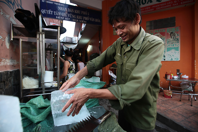 An ice cutter works in the early morning hours on Bui Vien Street in Ho Chi Minh City, Vietnam. Aug. 18, 2011.