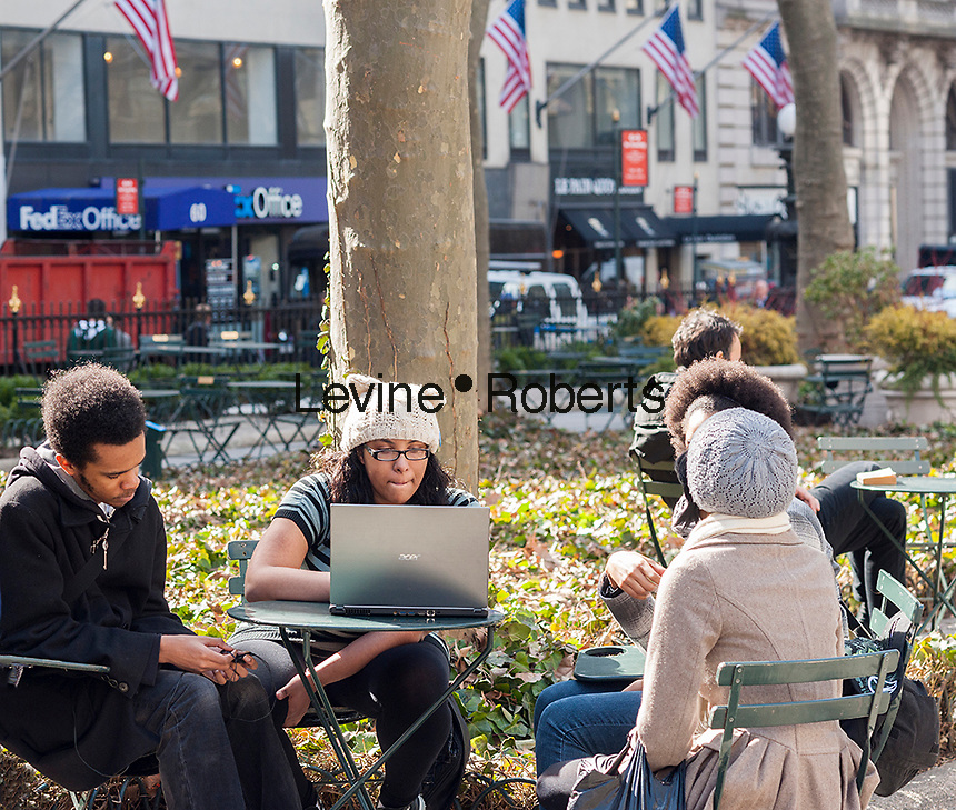 Teens in Bryant Park take advantage of the free wi-fi with their laptop computer in New York on Friday, March 21, 2014. Friday was the first full day of Spring heralding in balmy weather for the first half of the weekend. Sunday, the temperature will drop back into the 40's. (© Richard B. Levine)