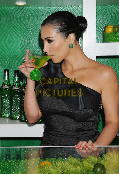 KIM KARDASHIAN.The Midori Melon Liqueur Trunk Show at Trousdale  in West Hollywood, California, USA..May 10th, 2011.half length dress black one shoulder green earrings  drink drinking side profile red nail varnish polish drink beverage .CAP/ROT/TM.© TM/Roth/Capital Pictures