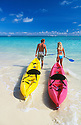 Couple with kayaks entering water; Lanikai Beach, Windward Oahu, Hawaii.