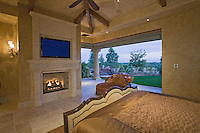 View of beautiful bedroom with fireplace, flatscreen TV and pocket doors that have been open to the outside