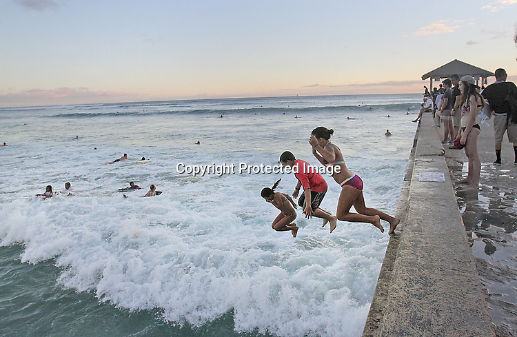 "A group of kids jumps off the Wall at Waikiki. The ""Wall"" at Waikiki is a favorite place for tourists and locals to hang-out to see the sunrise, sunsets, swim, surf or just to to meet friends."
