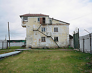 A guardhouse with administrative offices and rooms for meetings. Upstairs: living quarters. To the right: the entrance gate and barbed-wire fence. Perm province, Russia 2015