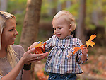 Happy two year old girl and her mother gathering fallen autumn leaves in a park
