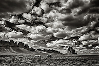 A black and white image of two horses grazing under a stormy sky with Shiprock in the distance