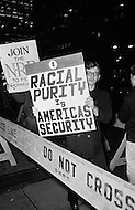 09 Dec 1969, Manhattan, New York City, New York State, USA --- An American protester holds a sign with Racial Purity is America's Security written on it while marching in front of the Waldorf Astoria Hotel where President Nixon is attending a National Football Foundation Dinner. President Nixon had promised an early end to the Vietnam war but in a speech on November 3 in 1969 he announced his plan of Vietnamization and continuation of the war and many protesters took to the streets later in the month to express their dissatisfaction. --- Image by © JP Laffont/Sygma/CORBIS