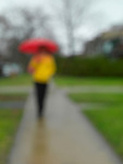 Woman in colorful clothes with un umbrella on a sidewalk in the rain. Artistically blurred out of focus photo.