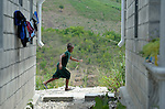 """A girl runs past houses in a model resettlement village constructed by the Lutheran World Federation in Gressier, Haiti. The settlement houses 150 families who were left homeless by the 2010 earthquake, and represents an intentional effort to """"build back better,"""" creating a sustainable and democratic community."""