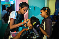 Graduating students from the beautician course practice for their final exams in the Guria Non-Formal Education center in the middle of the Shivdaspur red light district, Varanasi, Uttar Pradesh, India on 20 November 2013. These girls, daughters of women in prostitution, strive to break stigma and the cycle of prostitution by learning skills that will allow them to work in regular jobs.