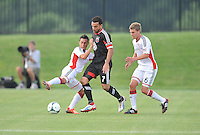 Dwayne De Rosario (7) of D.C. United goes against Diego Fagundez (14) left and  Scott Caldwell (6) right of the New England Revolution. D.C. United defeated the The New England Revolution 3-1 in the Quarterfinals of Lamar Hunt U.S. Open Cup, at the Maryland SoccerPlex, Tuesday June 26 , 2013.
