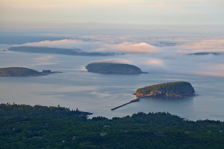 Fog envelopes the Porcupine Islands and Frenchman Bay, as viewed from the top of Cadillac Mountain, in Acadia National Park, Maine, USA