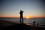Young Man Taking a Photos of People with Cell Phone, Silhouettes at Sunset on Beach