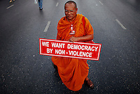 """A Buddhist monk holds a banner as he joins other supporters of former premier Thaksin Shinawatra in central Bangkok March 13, 2010. Anti-government protesters headed for Bangkok from the countryside on Saturday for what they are calling a """"million-man march,"""" aiming to paralyse the capital and topple a government they say is a front for unelected elites.  REUTERS/Damir Sagolj (THAILAND)"""