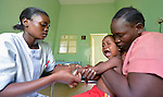 Rejoice Martin checks the IV on 2-year old Yusef as his mother, Flora Silva, restrains him, in the pediatric ward of the St. Daniel Comboni Catholic Hospital in Wau, South Sudan. Martin, a pediatric nurse, is a 2013 graduate of the Catholic Health Training Institute in Rumbek.
