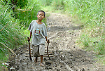 """A boy walks along a path in Nalapaan, one of seven villages near Pikit which has declared itself a """"space for peace."""" An initiative of the Immaculate Conception Parish in Pikit, the spaces for peace are villages where residents have told both the Moro Islamic Liberation Front and the Philippine military to desist from activity within the community. Residents also studied peacebuilding and conflict resolution,  and have made special efforts to increase interfaith dialogue and harmony."""
