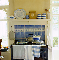 A blue and white glazed ceramic tile splash back echoes the colour of the crockery and the blue Aga in this kitchen