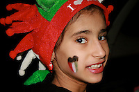Young girl smiling in her costume celebrating the Independence and National Days of Kuwait.  Flag colors on her face.  Hala February celebrations.