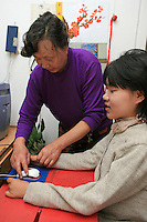 Song Fengying, Li Yan's mother, helps Li Yan to put her hands around the mouse to operate her computer in their home in Yinchuan, Ningxia Province, China, on May 7, 2007. 28-year-old Li Yan suffers from motor neuron disease also known as amyotrophic lateral sclerosis (or ALS), the same illness that has thereotical physicist Stephen Hawking. Li Yan asked China's National People's Congress (NPC) to consider a draft on euthanasia. Photo by Lucas Schifres/Pictobank