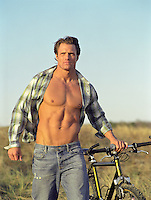 man with open shirt holding a bicycle outdoors