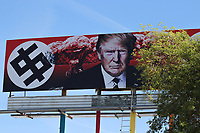 """(Phoenix, Arizona) – A new billboard on top of a Phoenix building is causing controversy after the artist who created it depicts U.S. President Donald Trump surrounded by nuclear explosions and two dollar signs in the fashion of Nazi swastikas. The billboard went up on Friday, March 18, 2017 on top of the design store """"11th Monk3y Apparel and Designs."""" The billboard is near Grand Avenue and 11th Avenue in Phoenix. The billboard was created by artist and activist Karen Fiorito, from Santa Monica, California. News reports indicate the billboard was commissioned by a Phoenix-based art gallery called La Melgosa. Photos by Eduardo Barraza © 2017"""