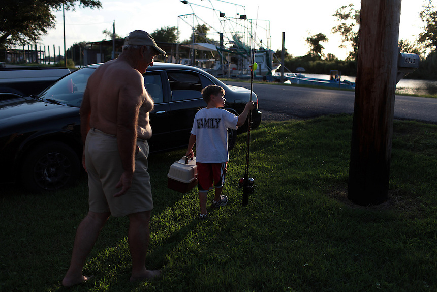 Howie Serigne showing Christian Guerra, 8, from St Bernard how to hook his reels in his camper at Delacroix Island, LA on September 01, 2010. Lazarus Gonzles talking with his cousin Howie Serigne visiting on the road.
