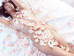 Beautiful nude asian woman lying in bed with pink rose petals covering her naked body, romantic concept