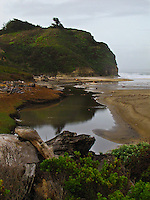 The south bluff at Pomponio State Beach twice counting its reflection in the lagoon.